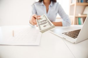 woman handing cash to camera